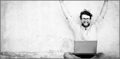 A happy man is sitting on his laptop and is mastering his prince2 certification